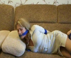 Hogtied girl struggles from couch